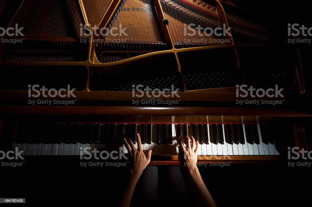 Woman's hands on the keyboard of the piano in night stock photo