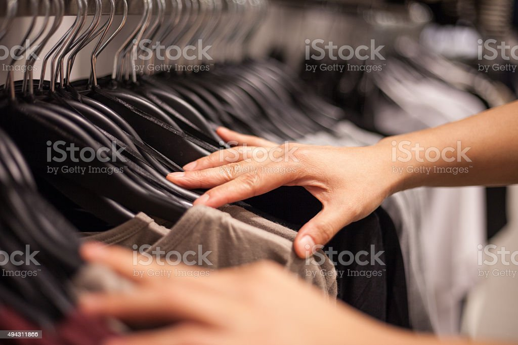 Woman's Hands Selecting Cloths in Fashion Store stock photo