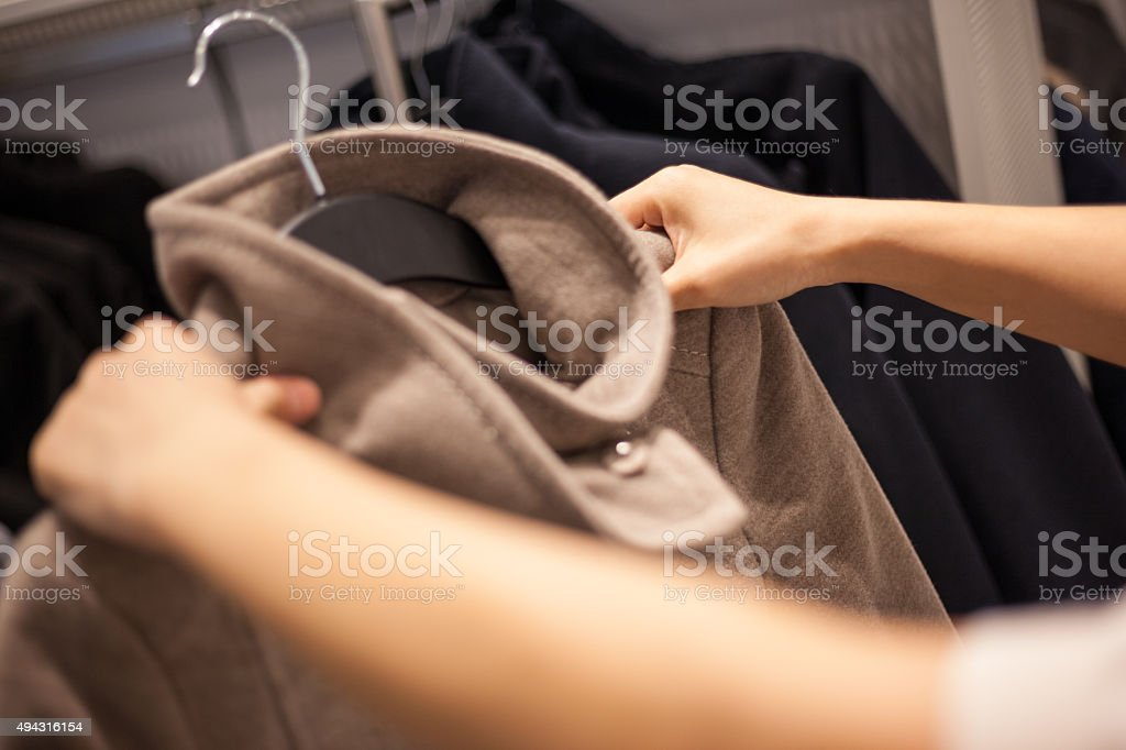 Woman's Hands Selecting Winter Coat in Fashion Store stock photo