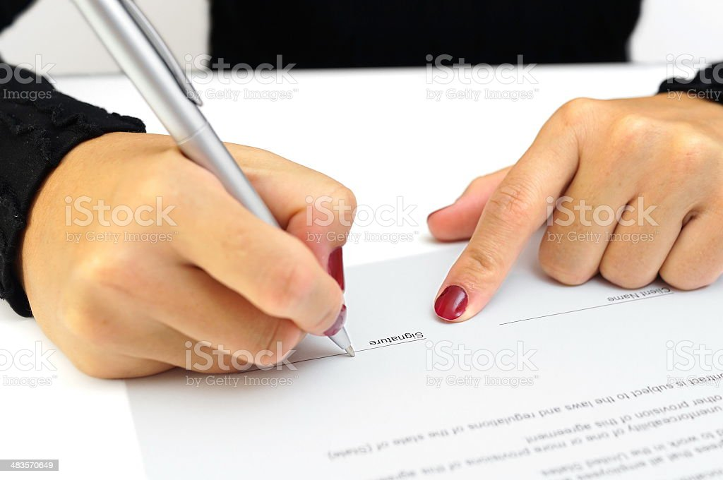Woman's hands signing contract document stock photo