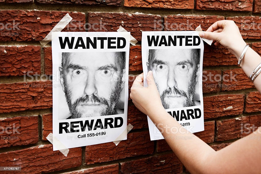 Woman's hands tape Wanted poster of man to brick wall royalty-free stock photo
