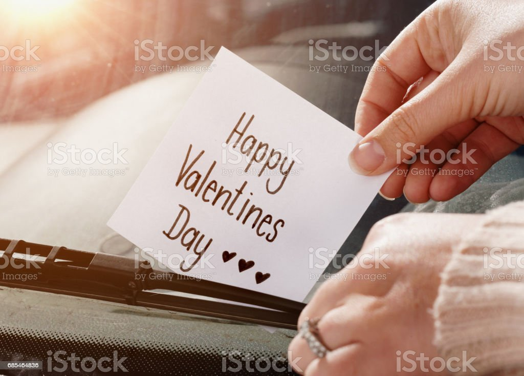 Woman's hands tuck note 'Happy Valentine's Day' under windscreen wiper stock photo
