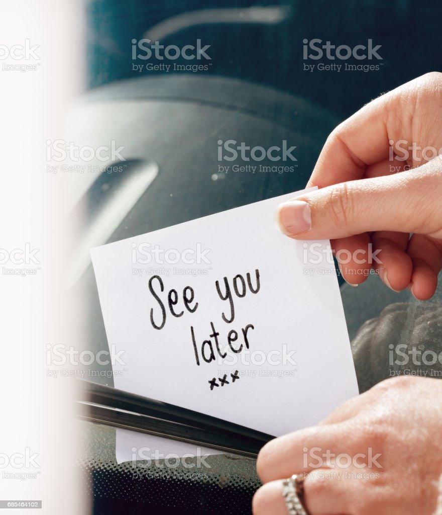 Woman's hands tuck note 'See you later' under windscreen wiper stock photo