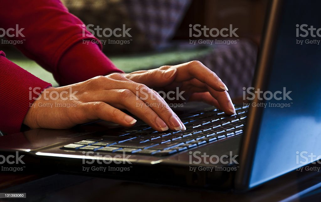 A woman's hands type on a notebook computer keyboard stock photo
