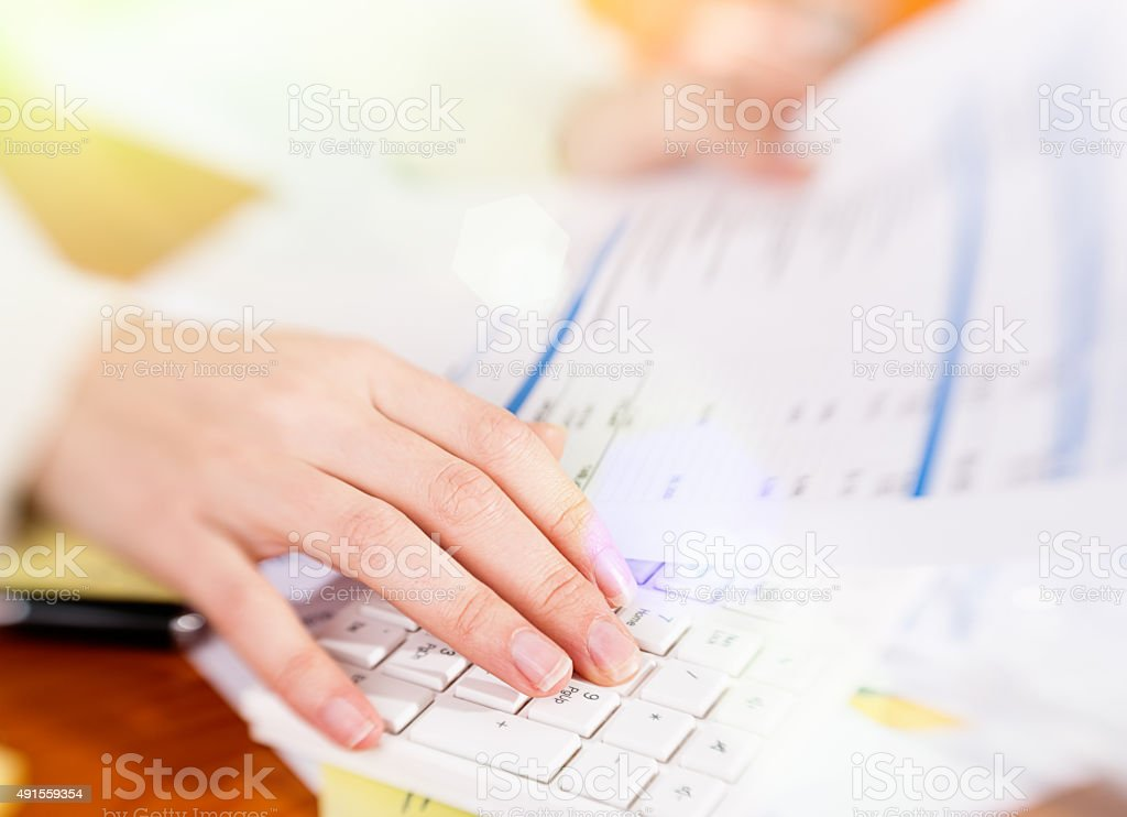 Woman's hands typing on computer keyboard in soft focus stock photo