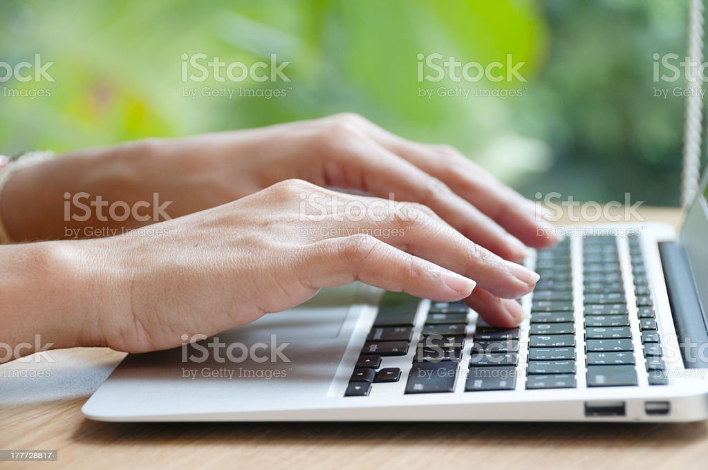 Woman's hands typing on laptop with greenery in background royalty-free stock photo