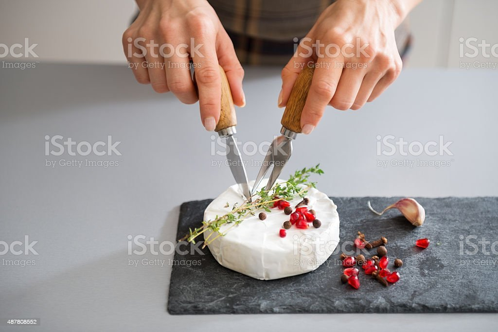 Woman's hands using cheese knife and fork to cut Camembert stock photo