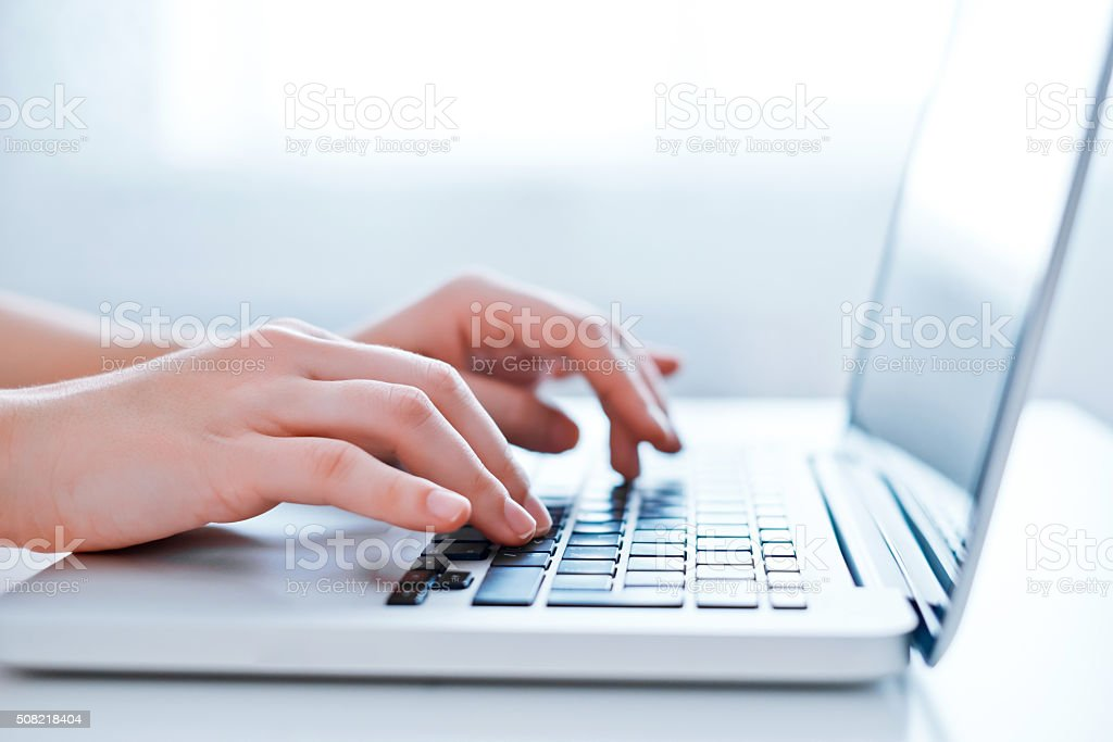 Woman's hands using laptop at the office stock photo