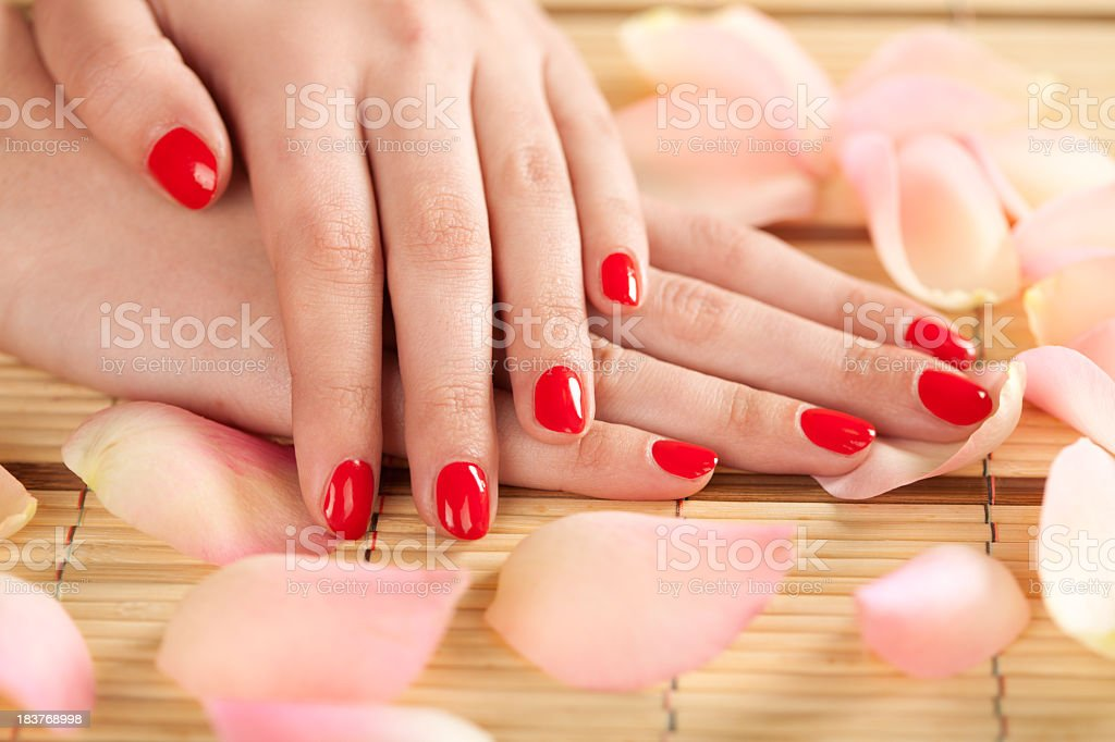 Woman's hands with red fingernails on bamboo table royalty-free stock photo