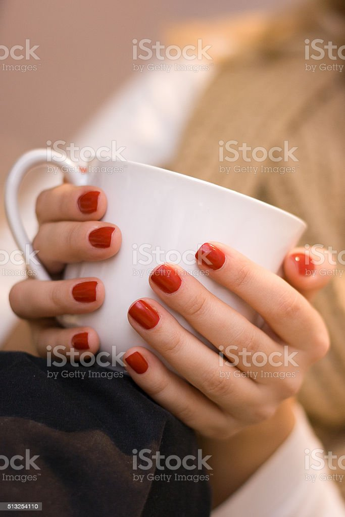 woman's hands with red nail polish holding a white cup stock photo