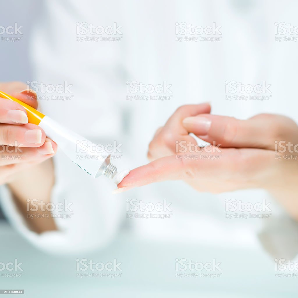 Woman's hands with white cream tube stock photo