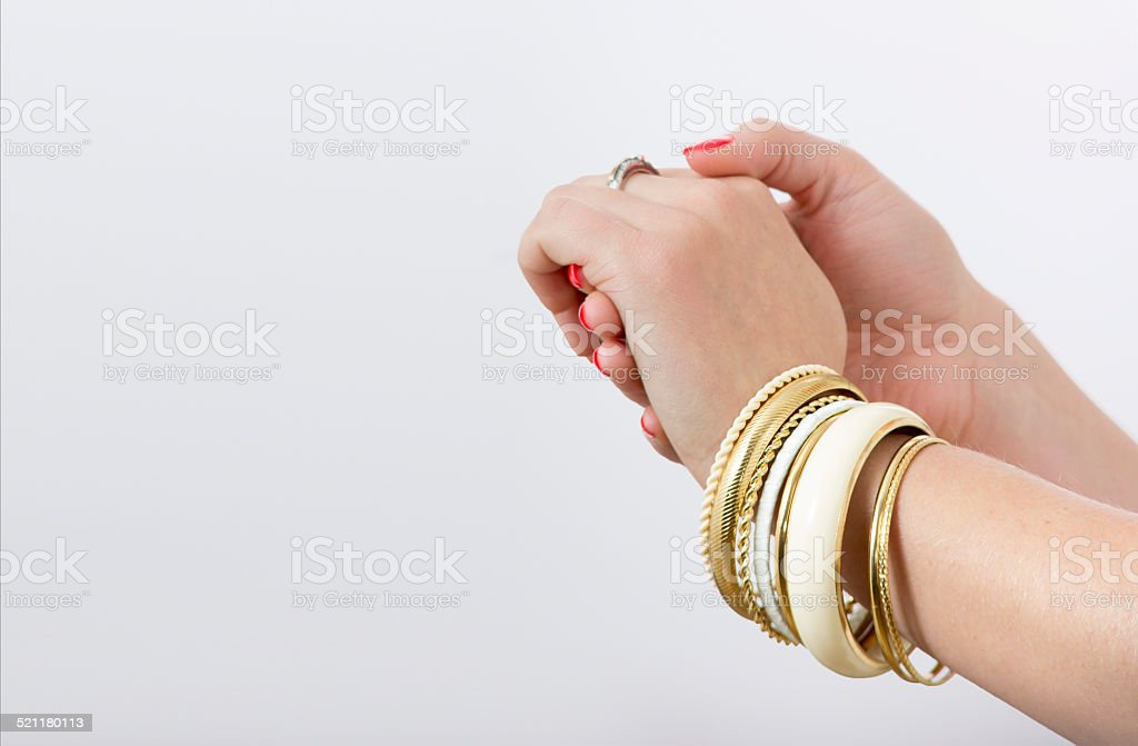 Woman's hands with yellow bracelets stock photo