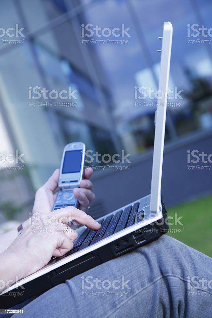 Woman's hands working on laptop outside office building, holding telephone royalty-free stock photo