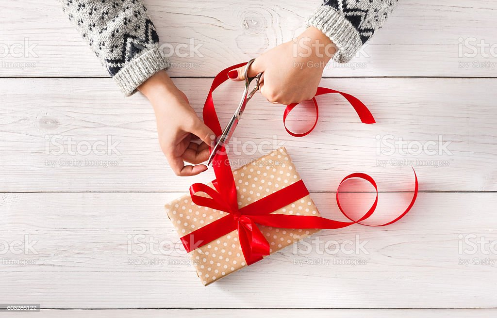 Woman's hands wrapping christmas holiday present iwith red ribbon stock photo