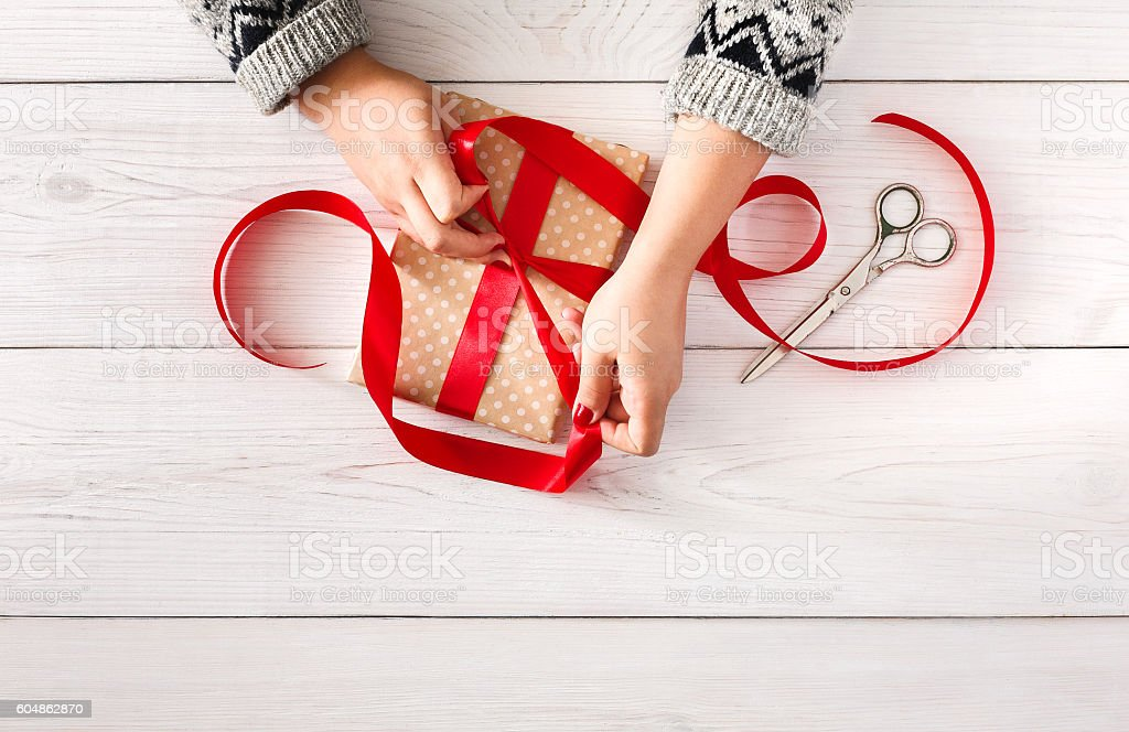 Woman's hands wrapping christmas holiday present with red ribbon stock photo