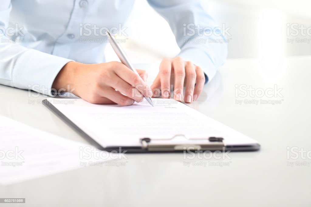 Woman's hands writing on sheet of paper in a clipboard and a pen; isolated on desk stock photo