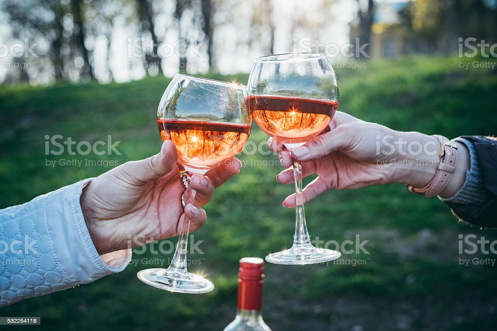 Womans holding 2 glasses of pink wine stock photo