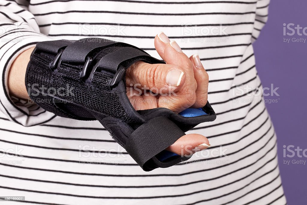 Woman's incapacitated hand wrapped in brace. stock photo