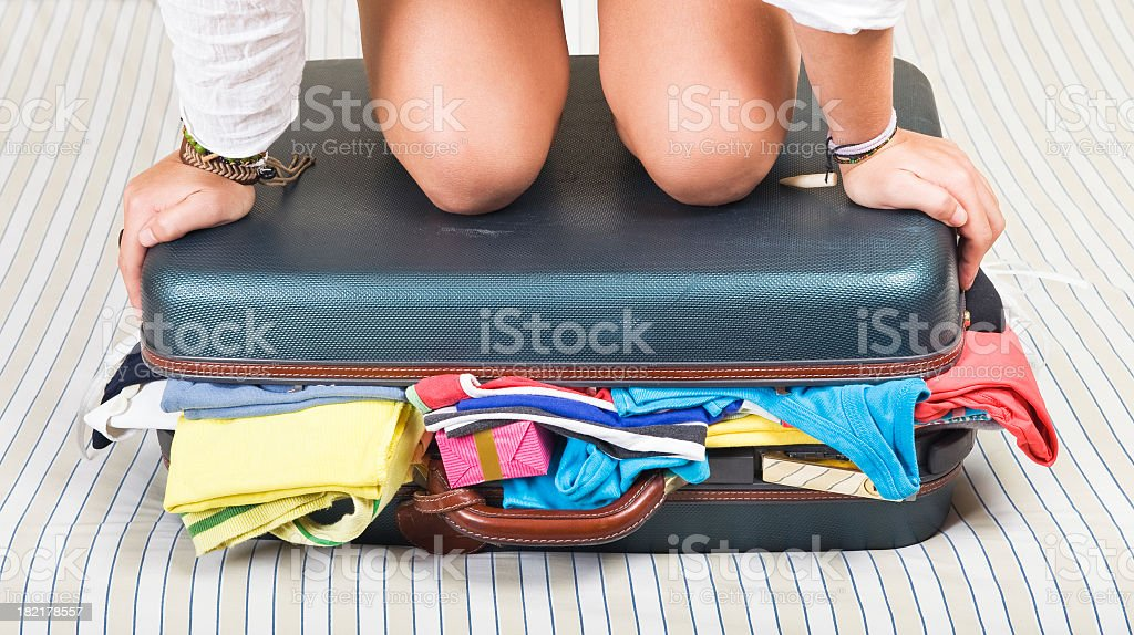 Woman's knees and hands on a suitcase full of clothes stock photo