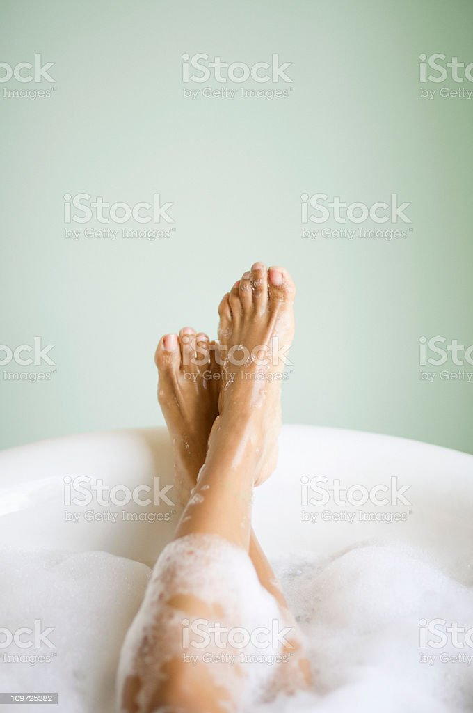Woman's Legs and Feet in Bathtub with Bubbles stock photo