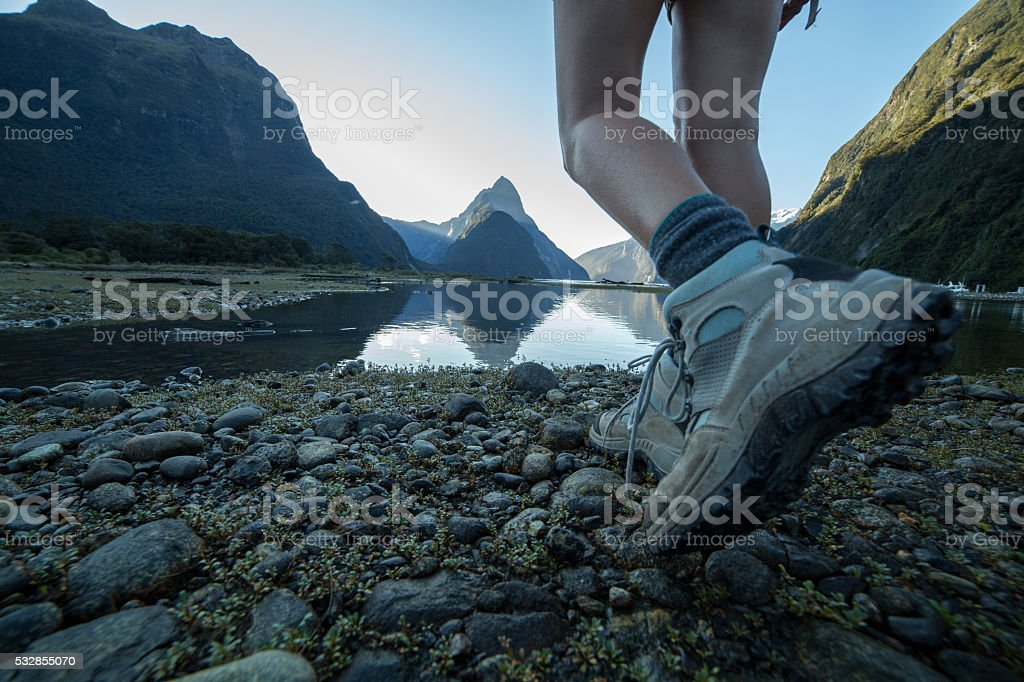 Woman's legs and hiking boots standing at Milford Sound, NZ stock photo