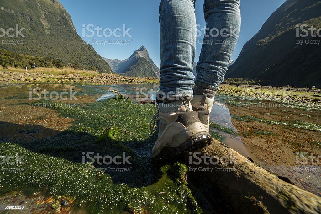 Frau Beine und Wanderschuhe stehend auf Baum Stamm – Foto