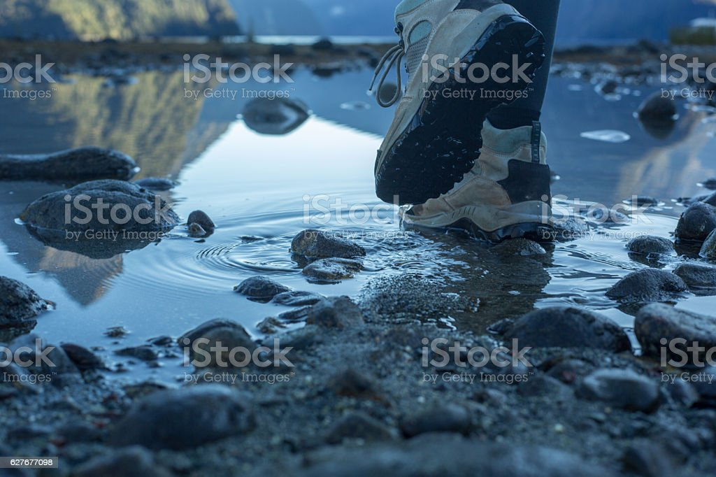Woman's legs and hiking boots walking on rocky trail stock photo