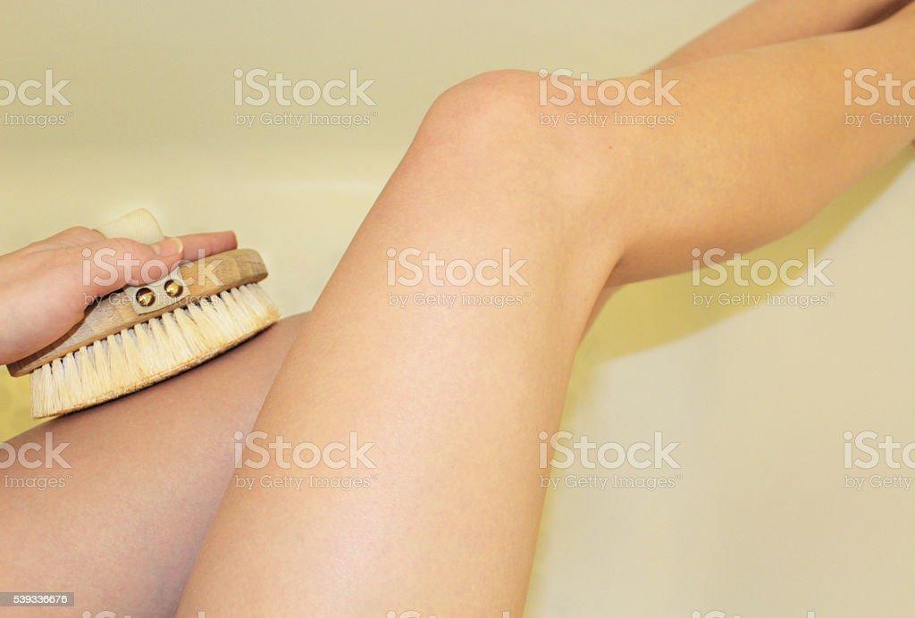 Woman's Legs Dry Body Brush Exfoliation stock photo