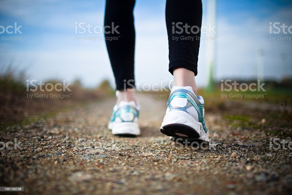 Woman's legs in black tights and white running shoes on dirt stock photo