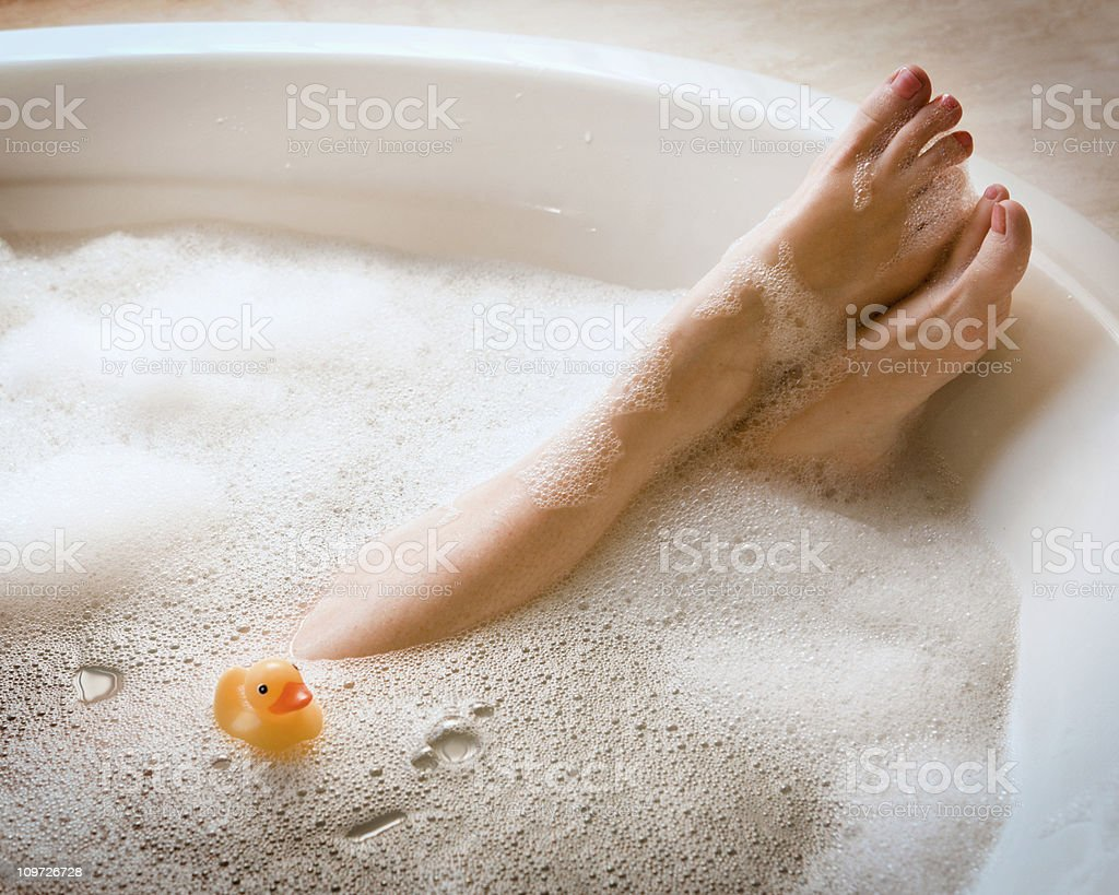 Woman's Legs in Bubble Bath with Ducky stock photo