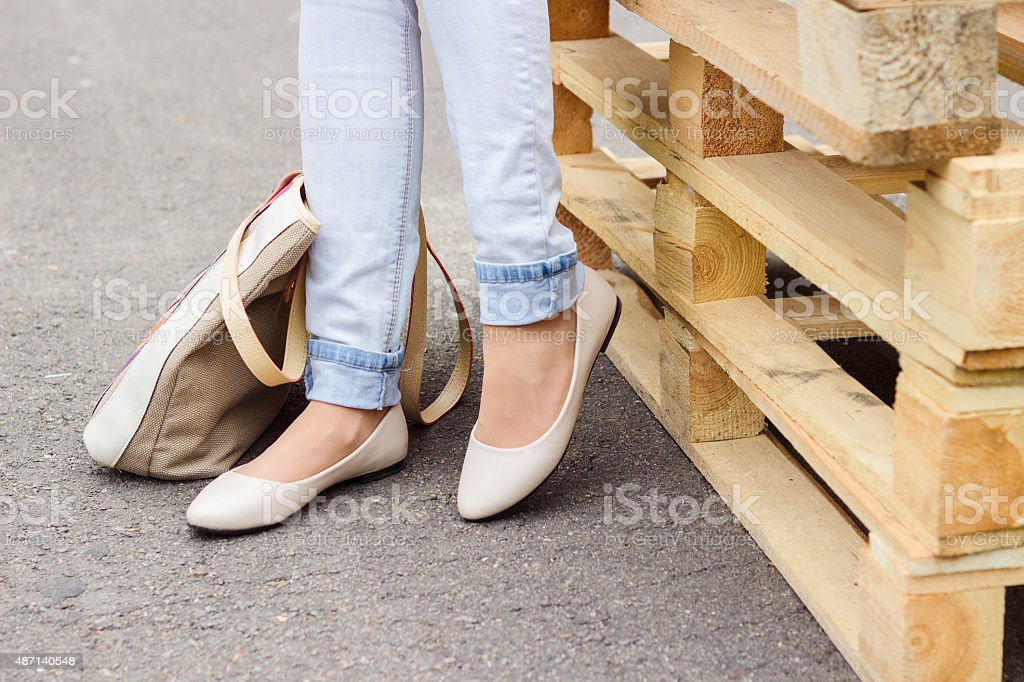 Woman's legs in jeans and flat shoes stock photo