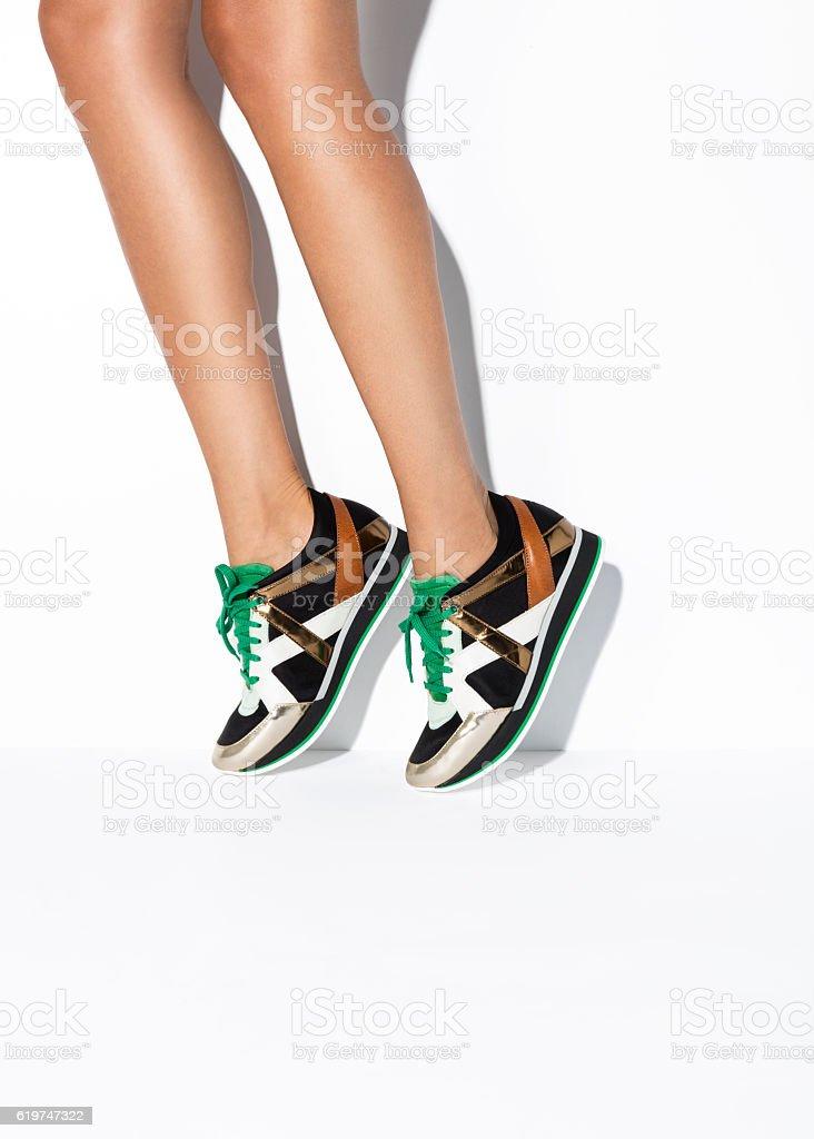 Woman's legs in sneakers stock photo