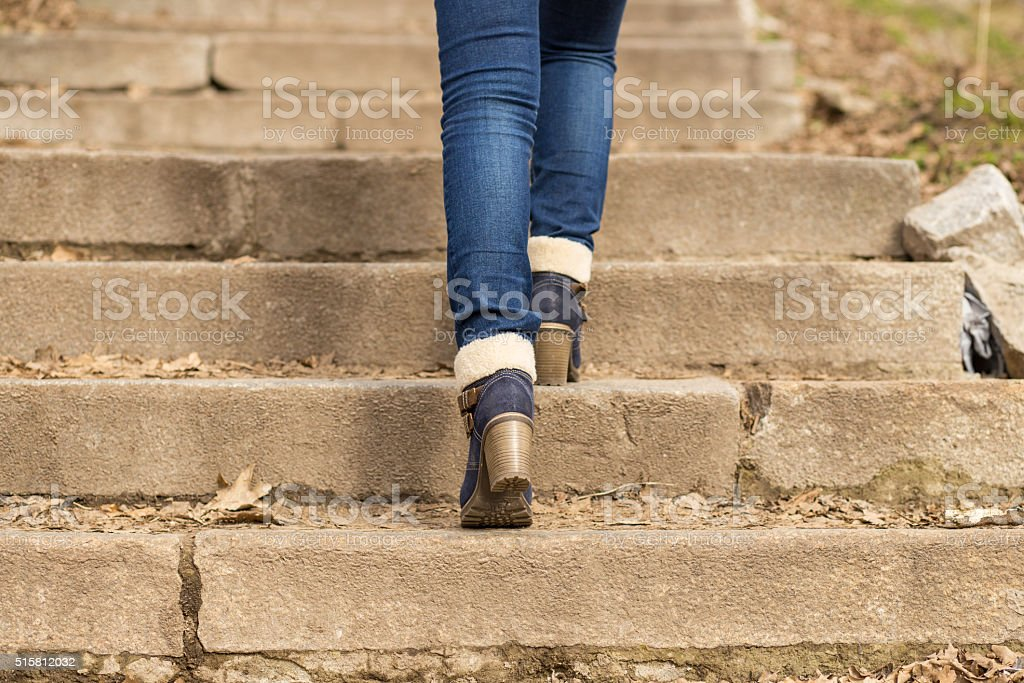 Womans legs in winter boots stepping on stairs stock photo
