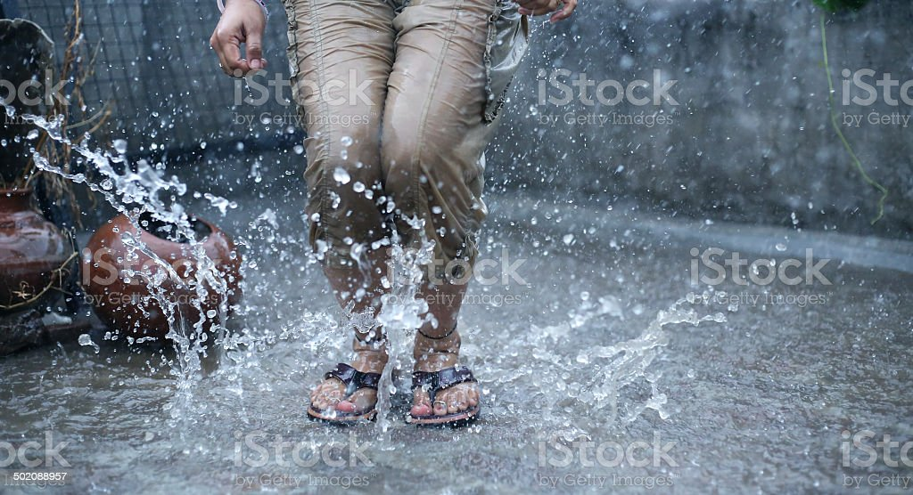 Woman's Legs jumping in the Rain stock photo