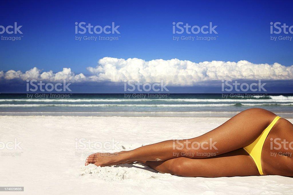 Woman's legs lying on a sandy beach on a bright sunny day stock photo