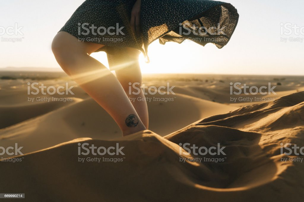 Woman's legs  on sand in the desert stock photo