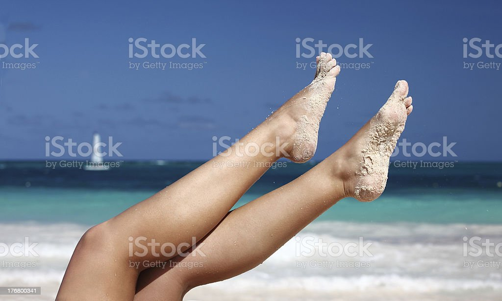 Woman`s legs on tropical beach background royalty-free stock photo