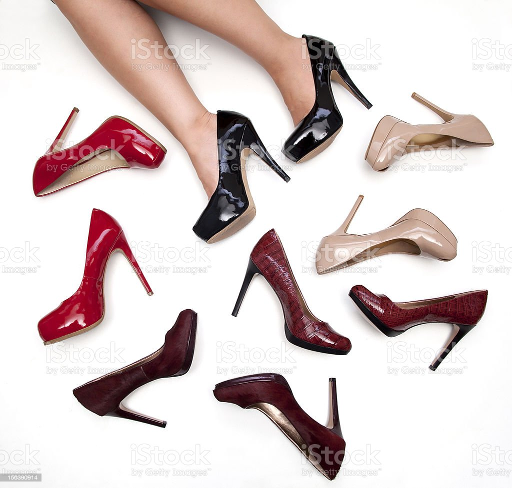 A woman's legs surrounded by different pairs of heels stock photo