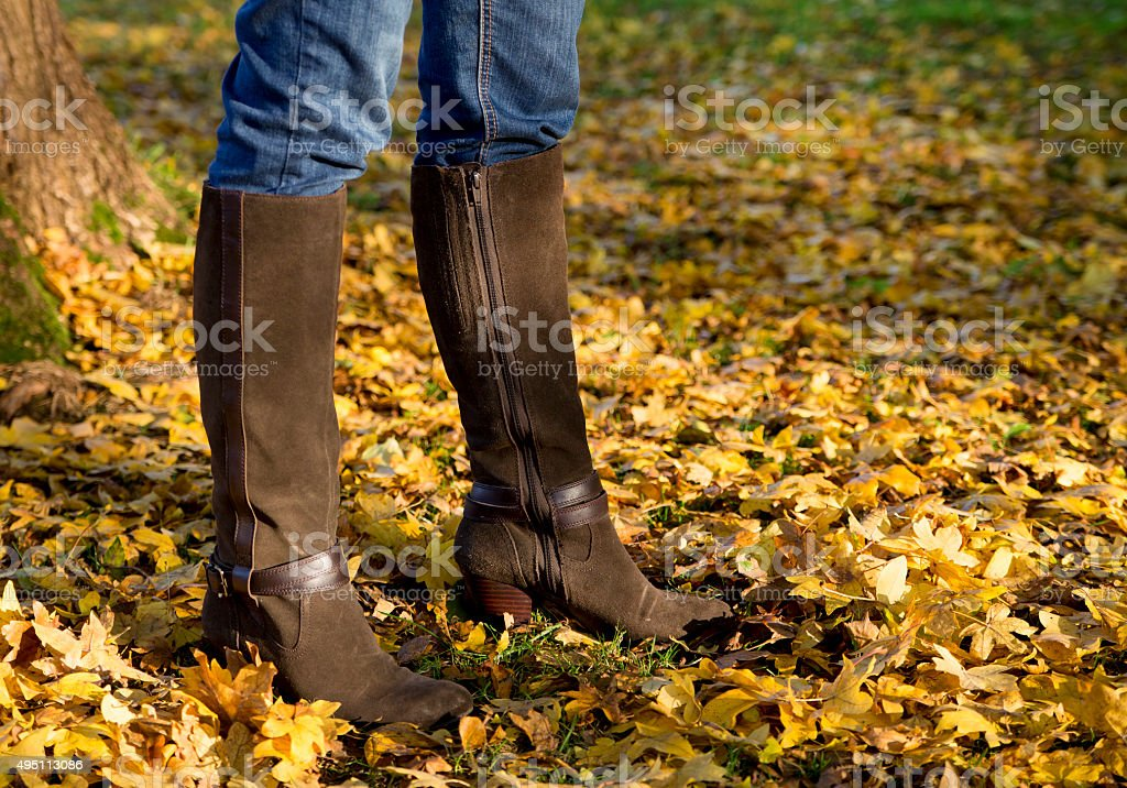 Woman's legs wearing leather boots standing among autumn leaves stock photo