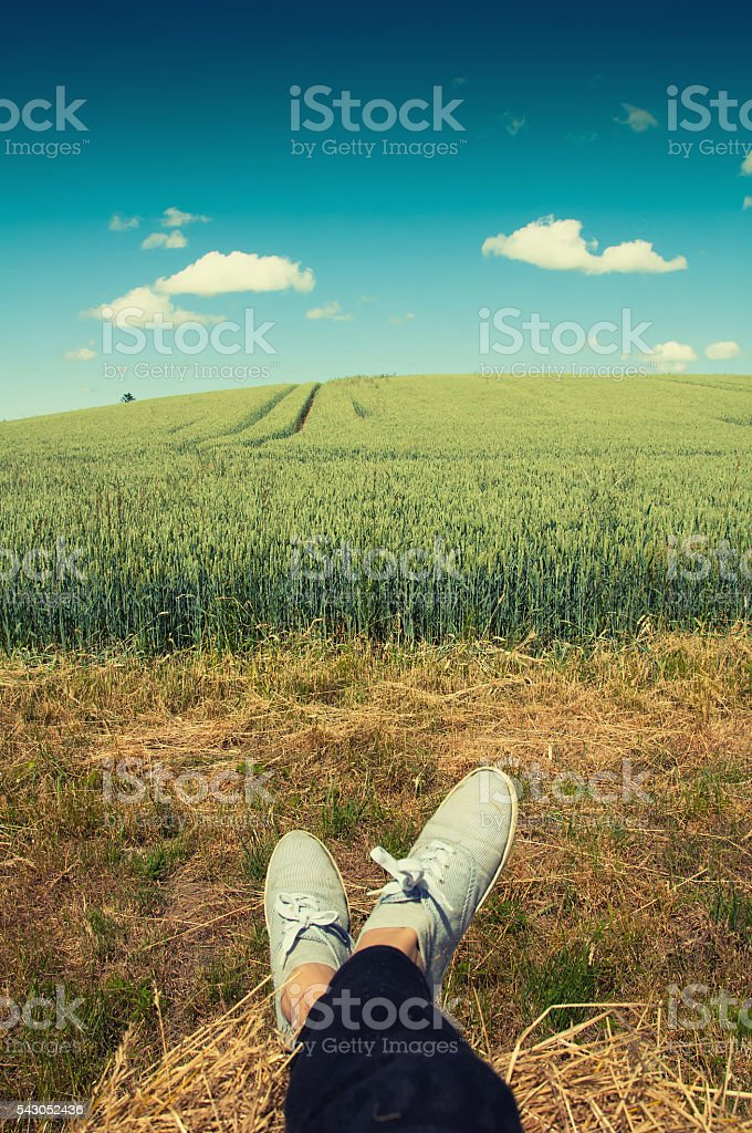 Woman's legs with blue shoes sitting on a bale stock photo