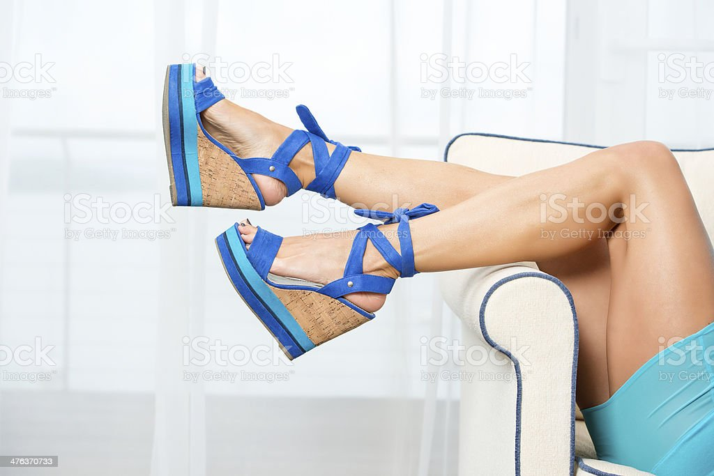 Woman?s legs with blue wedge style High Heels stock photo