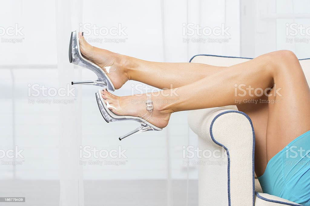 Woman´s legs with clear/transparent High Heels sandals stock photo