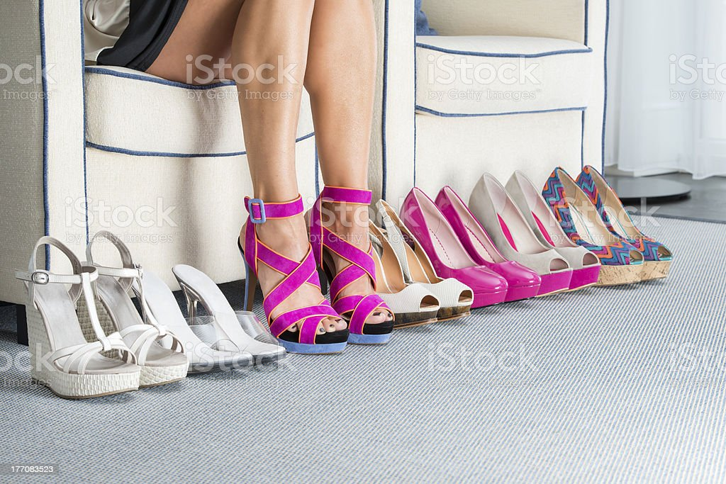 Woman's legs with row of various high heels stock photo