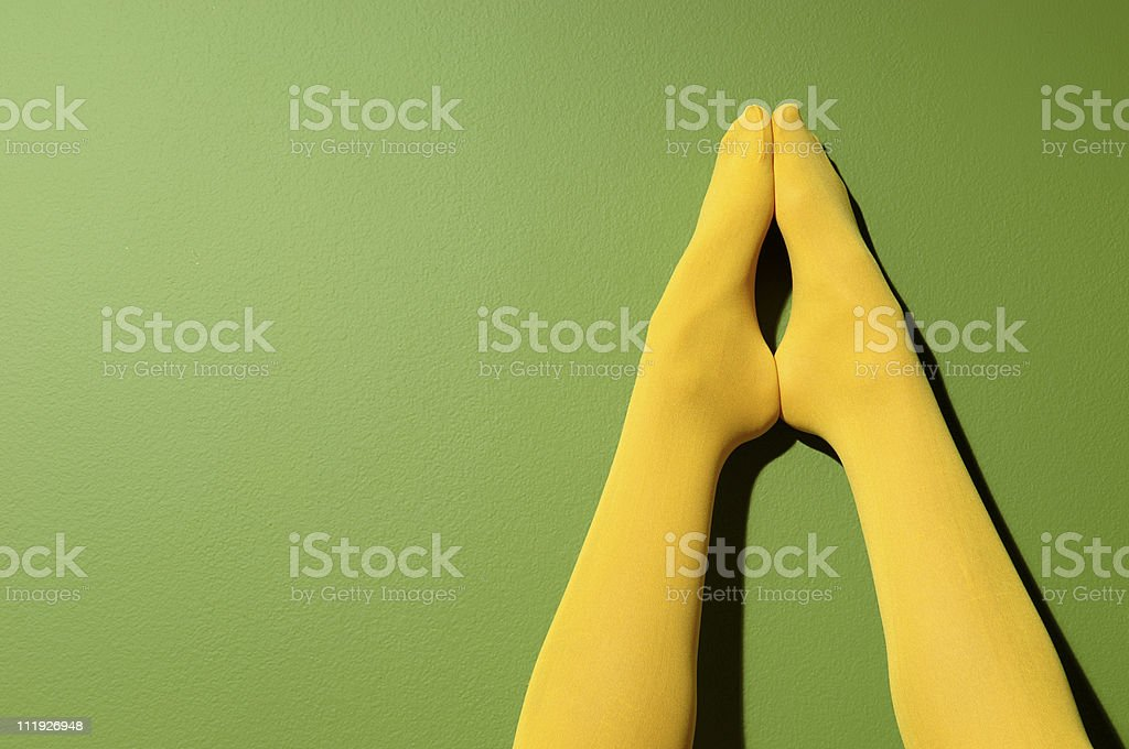 Woman's Legs Yellow Stockings Green Wall royalty-free stock photo