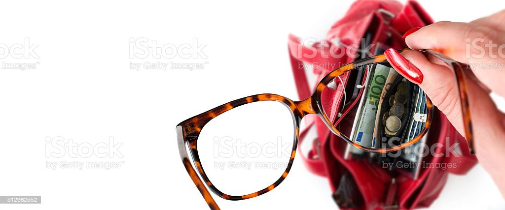 Woman's looks at wallet through her glasses stock photo