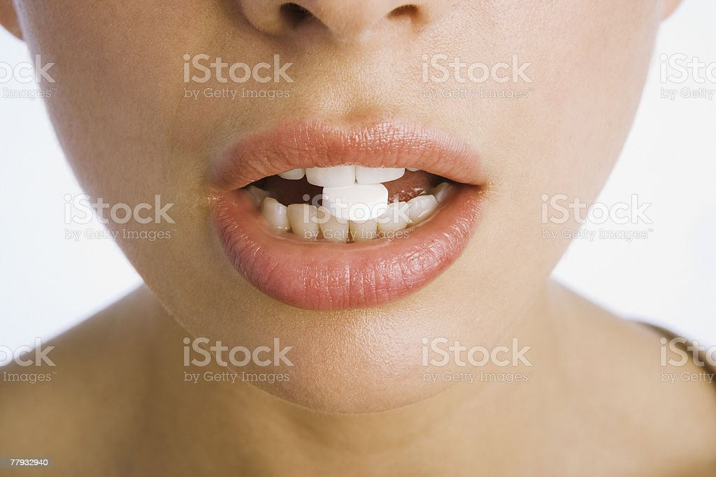Woman's mouth with pill in teeth royalty-free stock photo