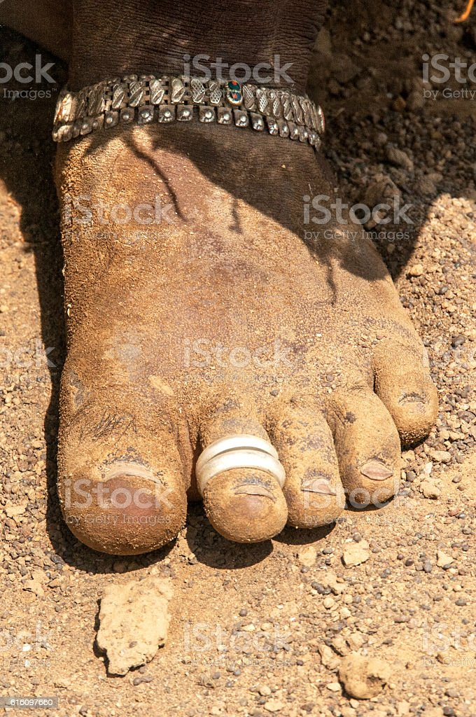 woman's muddy bare-foot with toe rings and silver ankle bracelet. stock photo