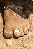 woman's muddy bare-foot with toe rings and silver ankle bracelet.