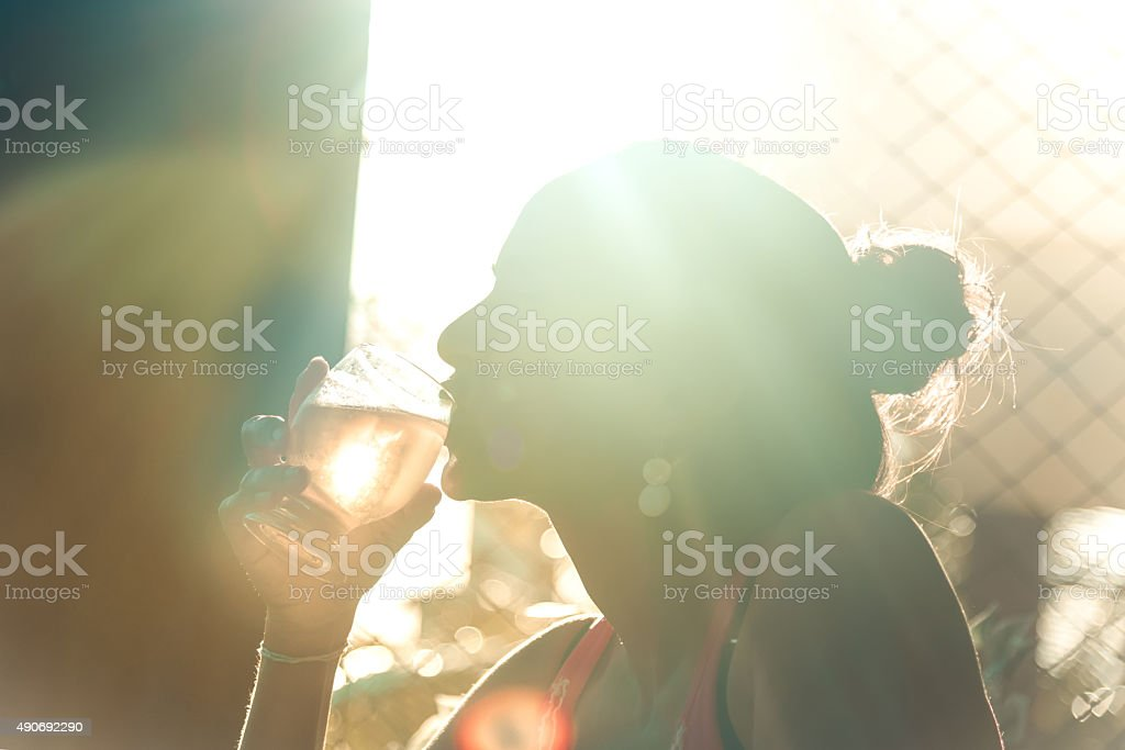 woman´s silhouette drinking beer in summer sun back light stock photo