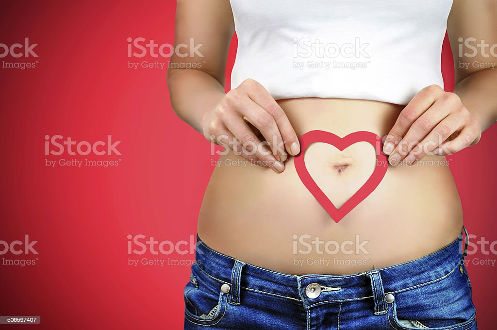 Woman?s stomach and a red heart shape around the navel. stock photo